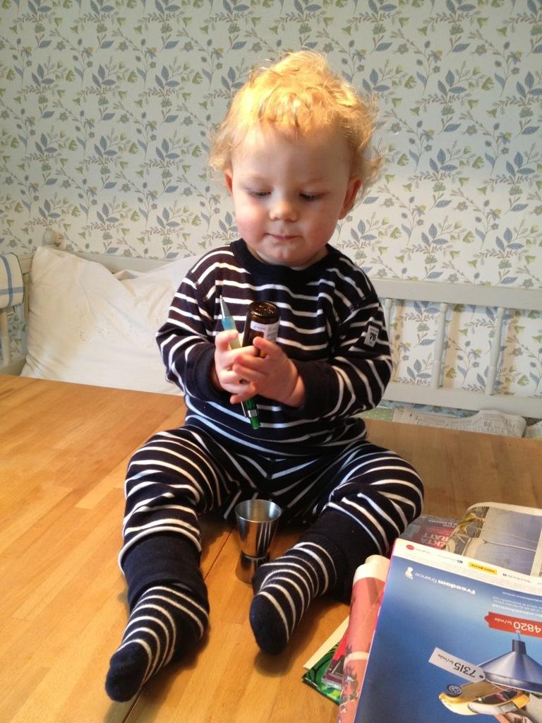 Ivar sitter på matbordet och leker med en penna och flaskan med D-droppar.