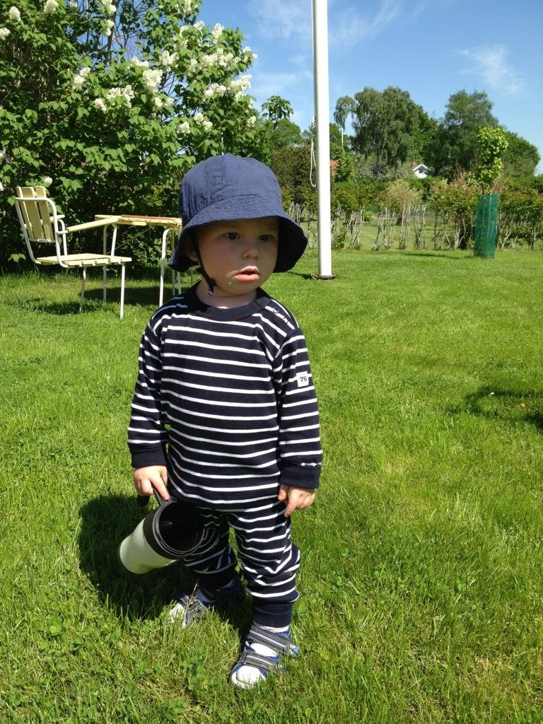 Ivar med solhatt på gräsmattan.
