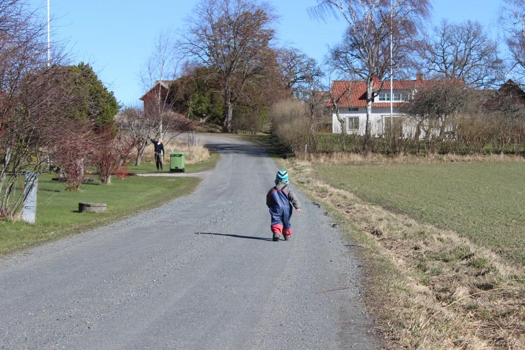 Ivar springer ifrån mig på grusvägen. Han är på väg mot en granne längre bort som har en traktor.