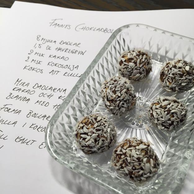 Några chokladbollar på ett glasfat. Under fatet ligger ett handskrivet recept på chokladbollar.