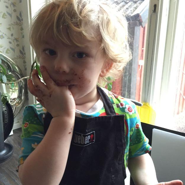 Ivar har chokladbollssmet i ansiktet och slickar av fingrarna.