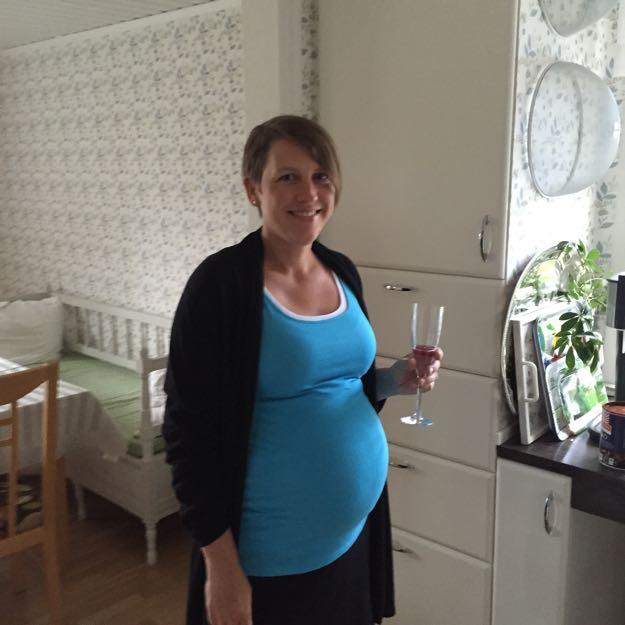Karin står hemma i köket i turkost linne och i övrigt svarta kläder. Gravidmagen börjar bli ganska stor.