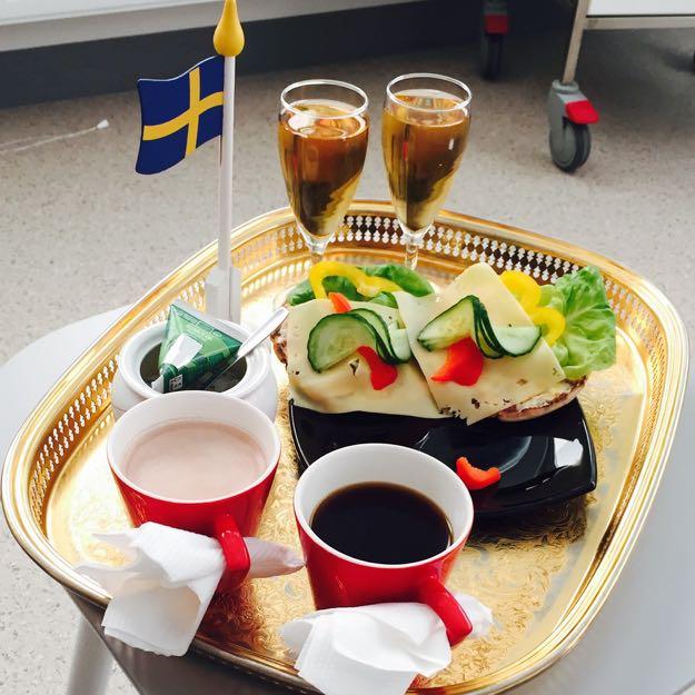 En bricka med en mugg kaffe, en mugg varm choklad, två glas på fot med äppeljos, ett fat med smörgåsar. Brickan pryds med en liten flaggstång med svenska flaggan hissad i trä.