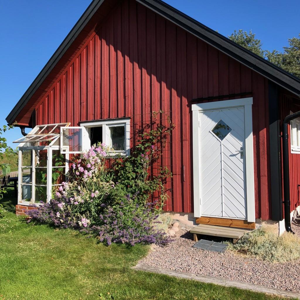 Röd husgavel med prunkande rabatt och en vit dörr.